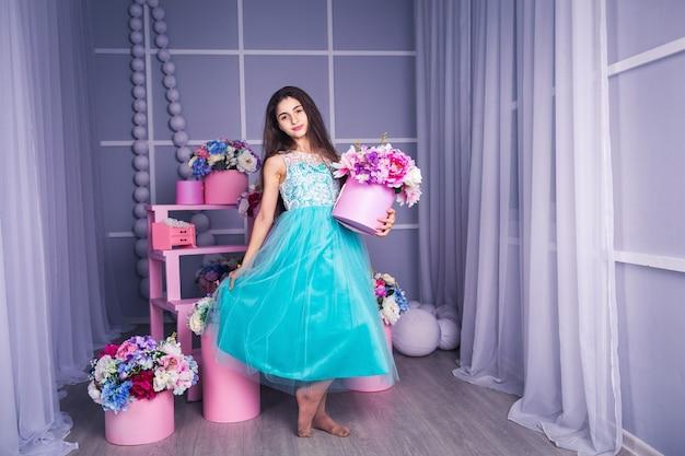 Belle fille en robe bleue en studio avec décor de fleurs dans des paniers. copiez l'espace.