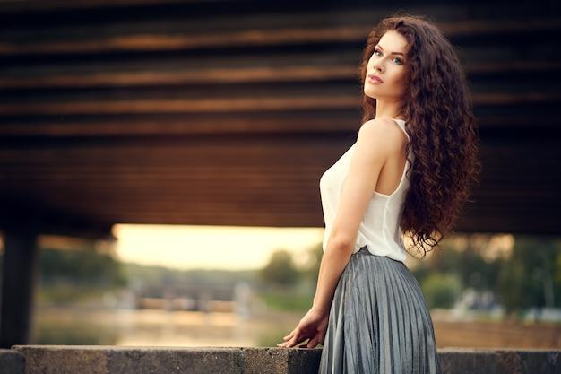 Belle fille en robe et cheveux bouclés souriant au coucher du soleil