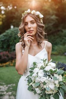 Belle fille en robe de mariée tenant un bouquet de fleurs blanches