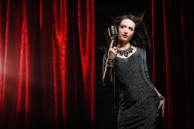 Belle fille en robe noire chantant dans le micro de la salle de concert
