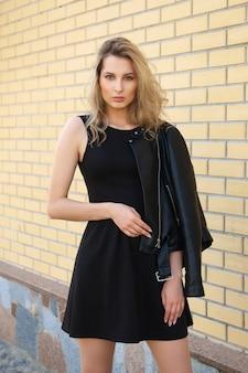 Belle fille en robe noire courte et veste en cuir dans la rue