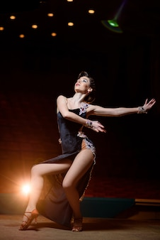 Belle fille en robe noire danse sur scène.