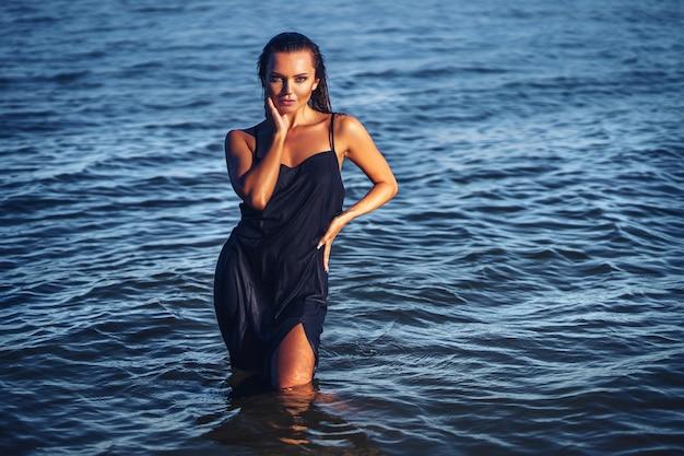 Belle fille en robe posant dans l'eau tropique fille belle peau bronzée joli visage