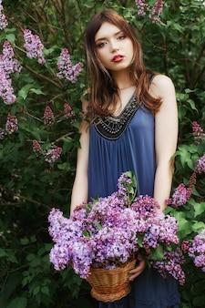 Belle fille en robe posant près d'un buisson