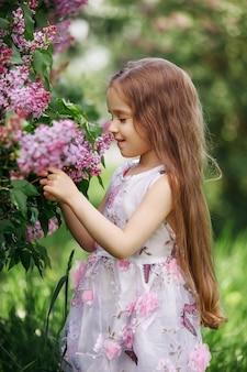 Belle fille en robe posant près de lilas de brousse