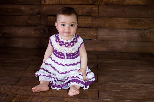Belle fille en robe rose sur un fond en bois