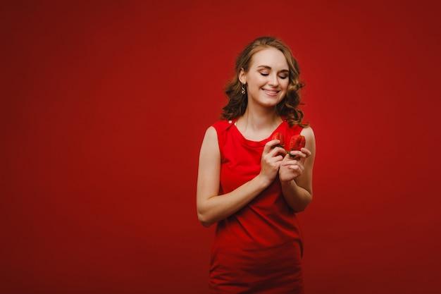 Une belle fille en robe rouge sur fond rouge tient une fraise dans ses mains et sourit