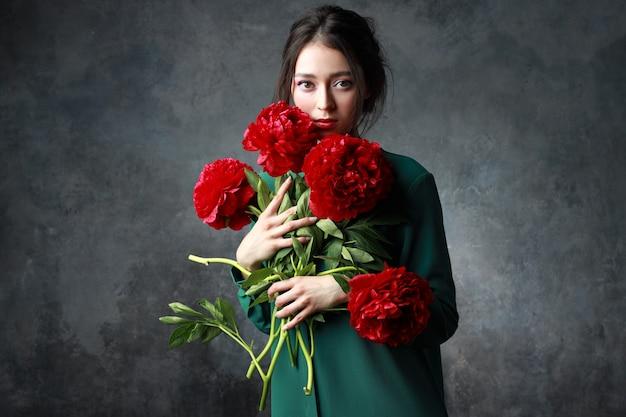 Belle fille en robe verte tendre avec bouquet de fleurs de pivoines dans les mains. mannequin ludique regardant la caméra