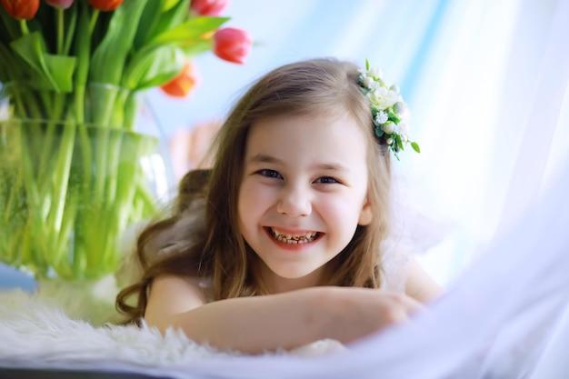 Belle fille en robes blanches avec un magnifique bouquet des premières tulipes. journée internationale de la femme. fille aux tulipes.