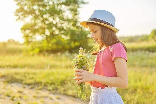 Belle fille romantique au chapeau, robe ramassant un bouquet de fleurs sauvages dans une prairie ensoleillée, paysage pittoresque, heure d'or, espace de copie. enfance, été, nature, beauté, concept d'enfants.