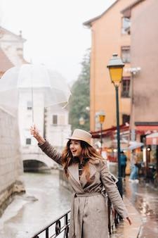 Belle fille romantique dans un manteau et un chapeau avec un parapluie transparent à annecy. la france. la fille au chapeau en france