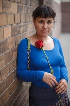 Belle fille avec une rose en ville. manteau bleu. photo de haute qualité