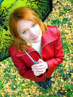 Belle fille rouge en veste de cuir avec parapluie