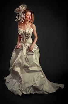 Belle fille rousse en élégante robe en papier