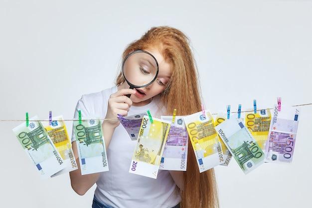Belle fille rousse examine les billets en euros à travers une loupe.