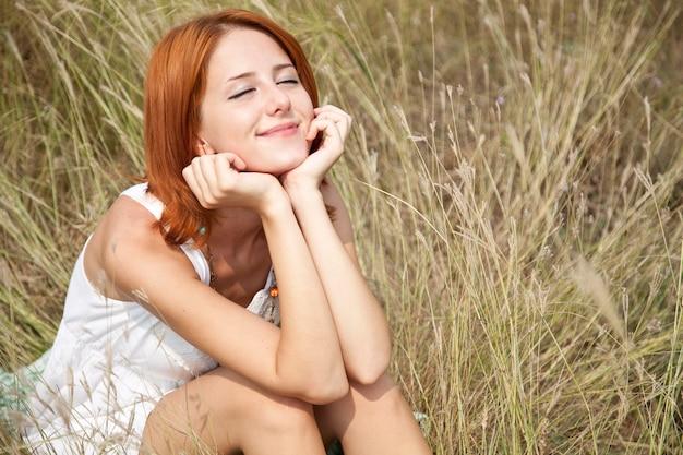 Belle fille rousse à l'herbe