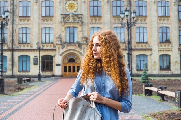 Une belle fille rousse de race blanche tient son sac à dos avec des livres