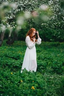 Belle fille rousse vêtue d'une robe blanche au milieu des pommiers en fleurs dans le jardin