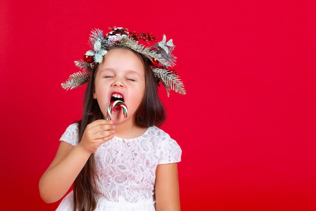 Belle fille s'amusant à manger une canne au caramel