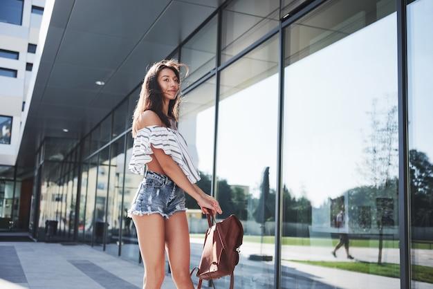 Belle fille avec un sac à dos, marchant le long de la rue de la ville par une matinée ensoleillée.
