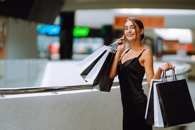 Belle fille avec des sacs à provisions regardant la caméra et souriant tout en faisant du shopping dans le centre commercial