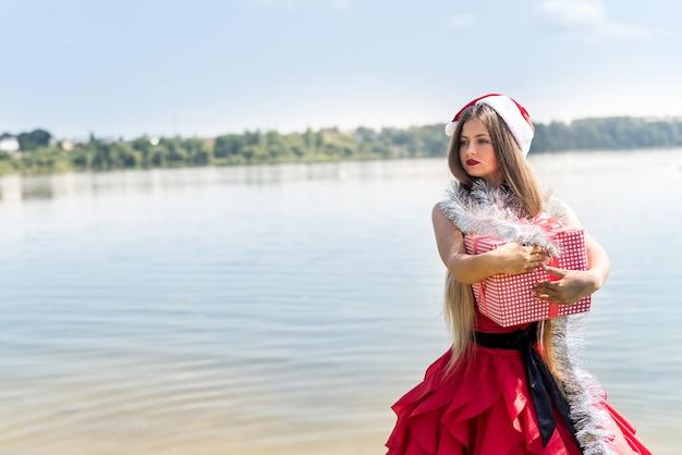 Belle fille santa tenant une boîte-cadeau au bord de la mer
