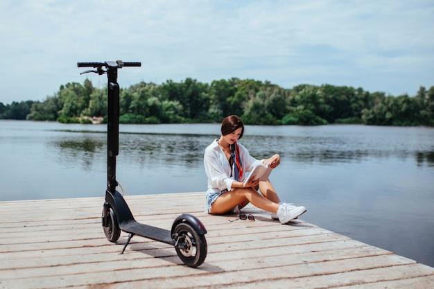 Une belle fille avec un scooter électrique lit un livre sur un pont en bois au bord de la rivière. concept de transport écologique et de soins de santé.