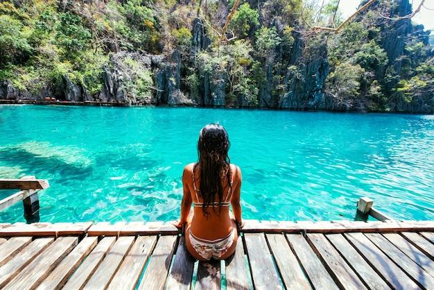 Belle fille se détendre au bord d'un lac. concept de vacances et de lieux tropicaux