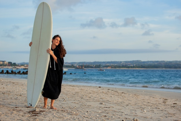 Belle fille se dresse sur la plage avec une planche de surf.