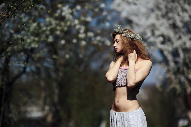 Belle fille se promène dans le jardin luxuriant vêtue d'une couronne