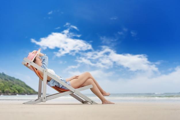 Belle fille se reposant sur une chaise au bord de la mer et levant la main pour attraper un chapeau.