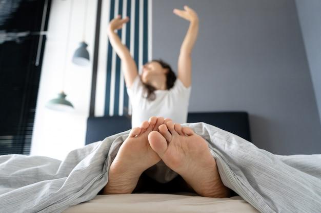 Belle fille se réveille de bonne humeur dans un appartement élégant. vue depuis les pieds