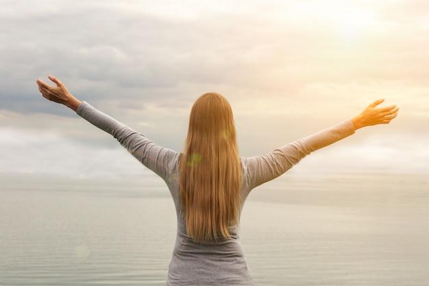 Une belle fille se tient au bord de la mer. les mains en l'air. le coucher du soleil. cours de yoga.