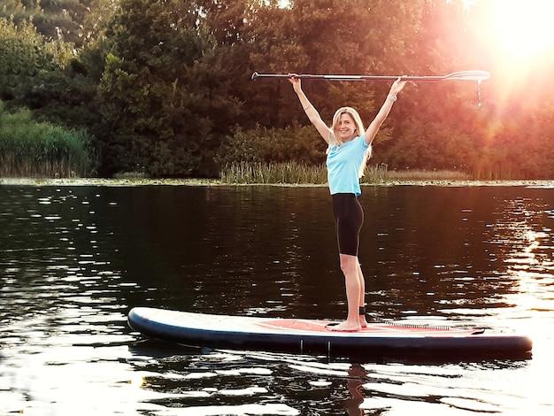 Une belle fille se tient sur une planche à pagaie sup et tient une rame au-dessus de sa tête dans le contexte de la rivière et de la forêt