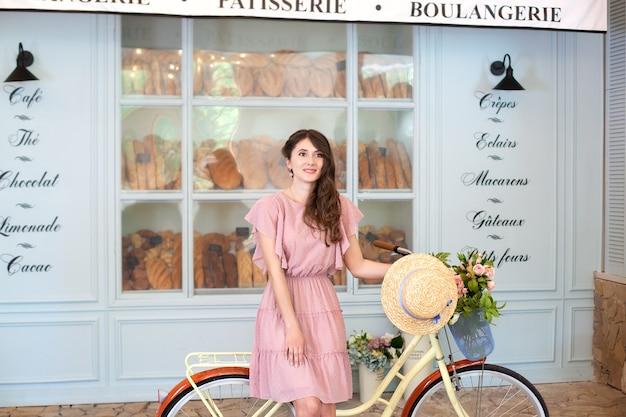 Belle fille se tient près du vélo avec un panier dans la rue de la ville pour aller travailler en vélo éco transport