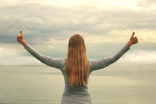 Une belle fille se tient sur le rivage, dos à la caméra. les mains en l'air. le coucher du soleil. cours de yoga.