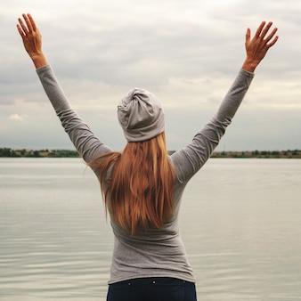 Une belle fille se tient sur le rivage. les mains en l'air. le coucher du soleil. cours de yoga.