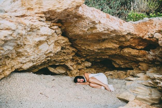 Belle fille se trouve dans un canyon de pierre sur la plage, grèce