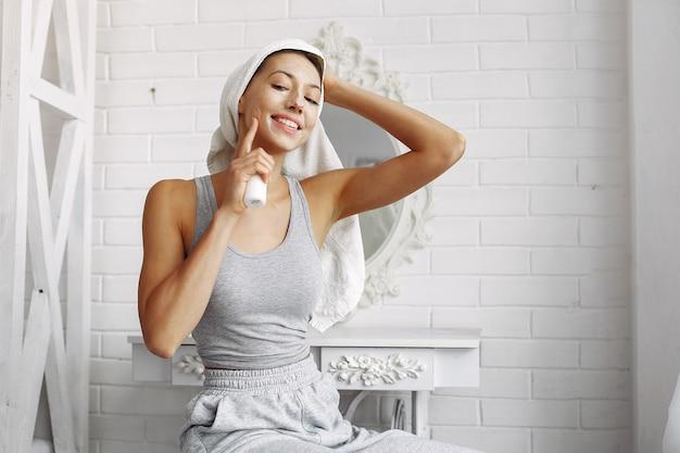 Belle fille avec une serviette à l'aide d'un produit de beauté