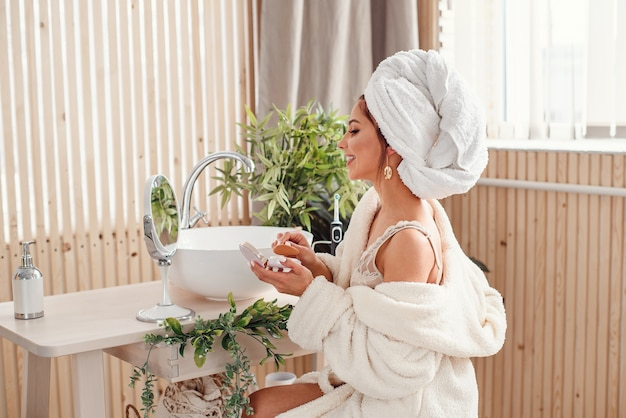 Belle fille avec une serviette blanche sur la tête habillée en peignoir fait le maquillage dans une salle de bain confortable