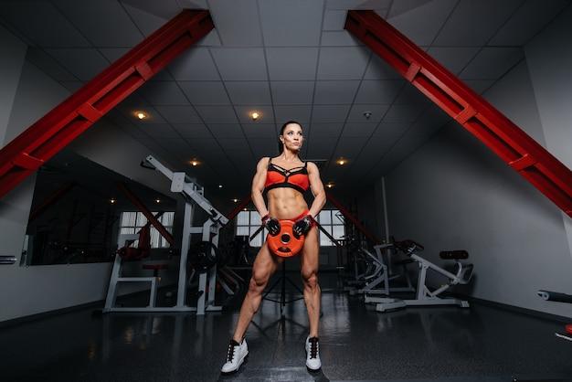 Belle fille sexy athlétique posant dans la salle de gym après un dur entraînement. fitness, musculation.