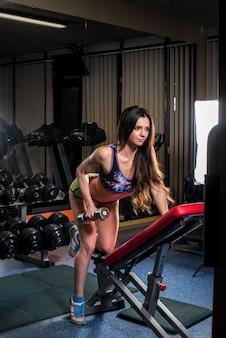 Une belle fille sexy athlétique s'entraîne et fait du fitness dans la salle de gym. fitness, musculation.