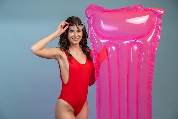 Belle fille sexy dans un maillot de bain une pièce rouge avec des lunettes de soleil et un matelas pneumatique rose
