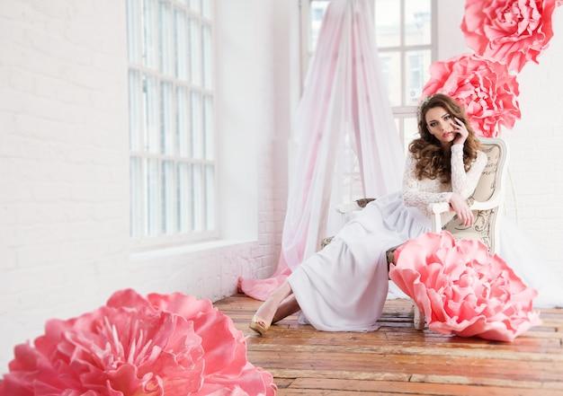 Belle fille sexy dans une robe longue avec un énorme fleurs roses assis près de la fenêtre