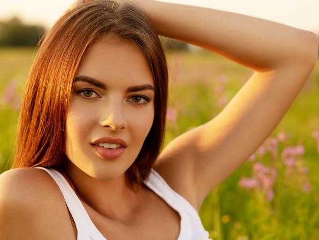 Belle fille sexy est sur la nature sur le fond de fleurs sauvages de printemps.