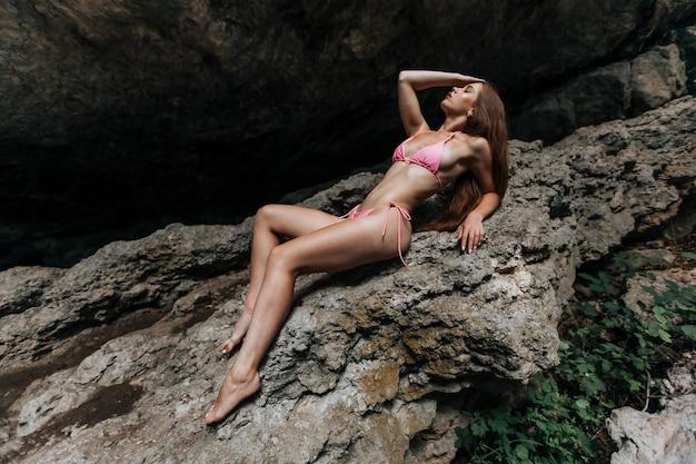 Une belle fille sexy en maillot de bain est allongée sur les rochers