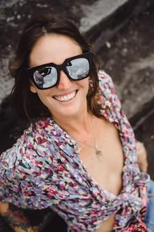Belle fille en short en jean avec de longues jambes, vêtu d'une chemise colorée et des lunettes de soleil