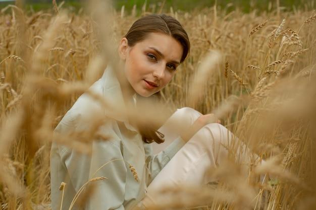 Belle fille slave dans des vêtements légers, assise dans un champ de blé.