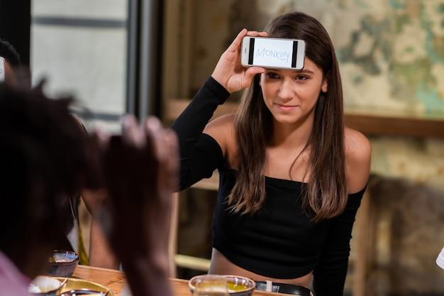 Une belle fille avec son smartphone sur son front assis à la table avec des amis et essayant de deviner un mot écrit sur son écran
