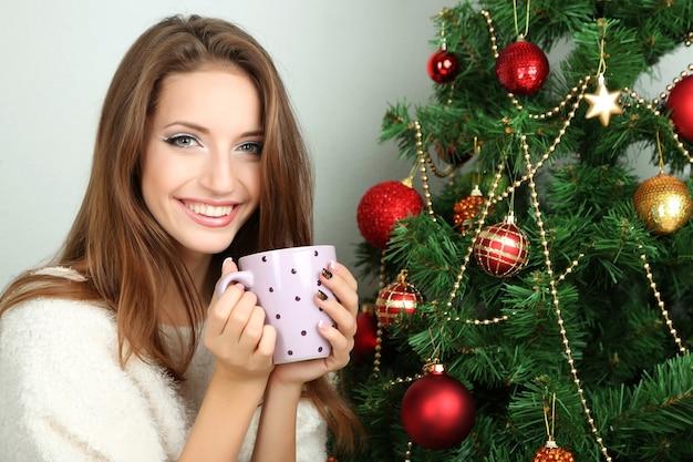 Belle fille souriante assise près de l'arbre de noël